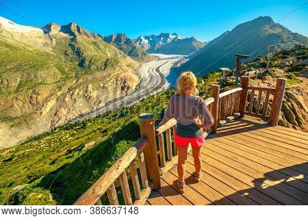 Tourist Woman From Viewing Platform Looking Alpine Glacier. Aletsch Glacier From Moosfluh Viewpoint