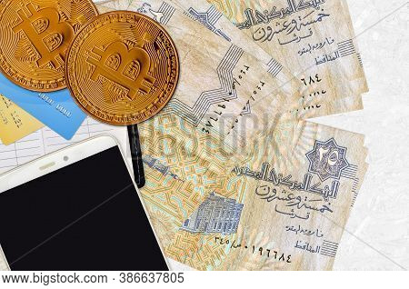 25 Egyptian Piastres Bills And Golden Bitcoins With Smartphone And Credit Cards. Cryptocurrency Inve