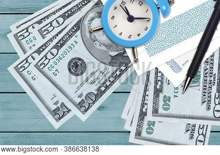 50 Us Dollars Bills And Alarm Clock With Pen And Envelopes. Tax Season Concept, Payment Deadline For