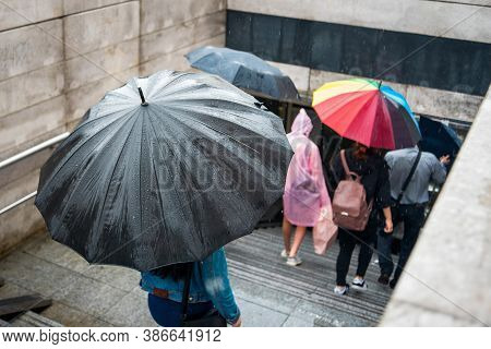 People With Umbrellas Descend Into The Underpass. Cityscape On A Rainy Day. Umbrella With Raindrops.