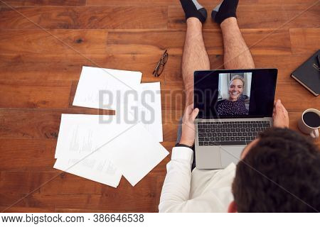 Businessman Wearing Loungewear And Shirt And Tie For Video Call On Laptop Working From Home