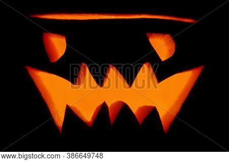 Evil Orange Glowing Lantern-jack Carved From A Pumpkin For The Holiday Halloween Close-up In The Dar