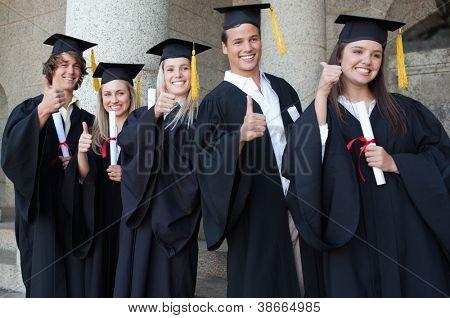 Absolventen posieren die Daumen-Up vor der Universität