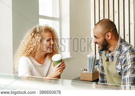 Smiling Blonde Woman Talking To A Waiter Of A Coffee Shop At The Counter