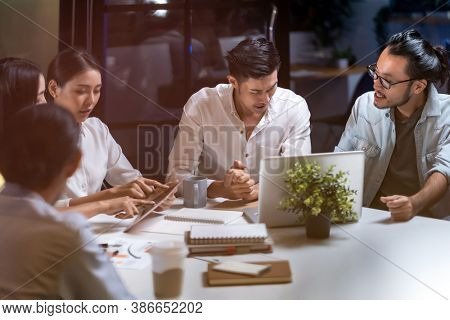 Work late concept of Interracial asian business team brainstorm idea at office meeting room at night. Work hard deadline and overtime working and new business start up concept.