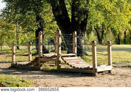Wooden Play Bridge For Children, Located In The Park Among The Trees. Outdoor Play Facilities. Bridg