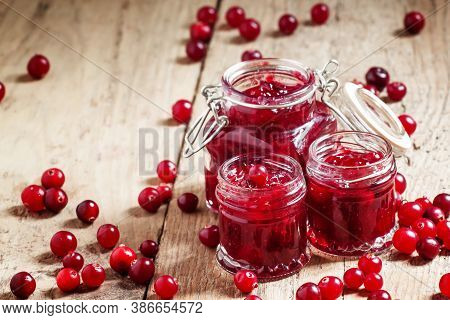 Delicious Cranberry Jam In Glass Jars And Fresh Cranberry On An Old Wooden Background In Rustic Styl
