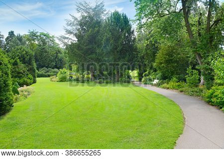 Green grass in meadow and footpath in picturesque summer park.