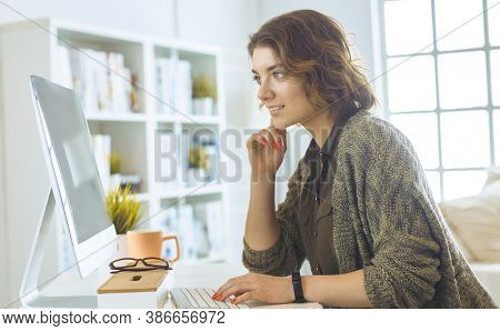 Young woman or student using tablet computer at home