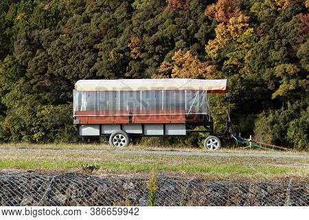 The Trailer On The Grassy Hill And Background Mountain Range. The Drawbar Trailer For Tourist Passen