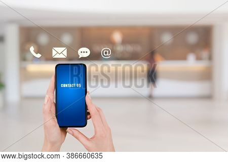 Call Center And Contact Us Concept : Hand Holding And Showing Smartphone With Contact Icons Symbol A