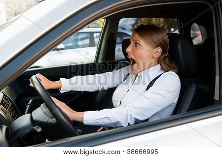 scared woman driving the car and honking
