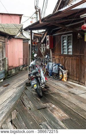 George Town, Penang, Malaysia - December 1, 2019: Motorcycle And Bicycles On Wooden Sidewalk Of The