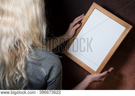 Partial View Of Young Blond Woman Holding Wooden Frame, Dark Background, Mockup, Blank Space