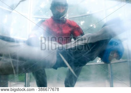 Woman With Instructor Is Flying In Aerodynamic Tube, View From Outside. Instructor Is Holding Human