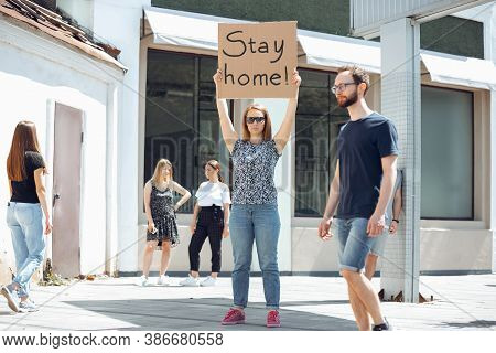 Stay Home. Dude With Sign - Woman Stands Protesting Things That Annoy Her. Solo Demonstration Right