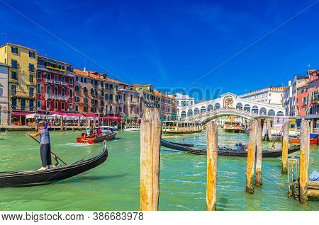 Venice, Italy, September 13, 2019: Gondolier And Tourists On Gondola Traditional Boat Sailing On Wat