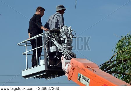 Workers on a mobile mechanical car lift cut tree. September 24, 2020. Near Kiev,Ukraine
