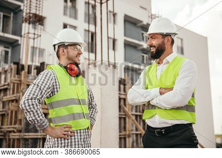 Cheerful Men In Helmets And Waistcoats Smiling And Looking At Each Other While Talking During Break