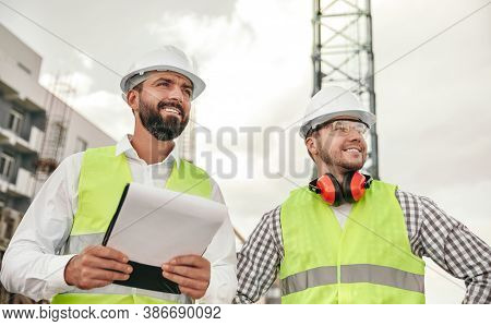 From Below Of Positive Confident Diverse Male Engineers In Waistcoats And Hardhats And With Document