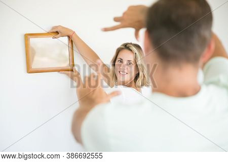 Caucasian Couple Hanging Picture On Wall In Their New House. Smiling Pretty Blonde Woman Holding Fra