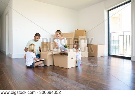 Happy Parents And Two Kids Moving Into New Empty Apartment, Sitting On Floor Near Open Boxes. Wide S