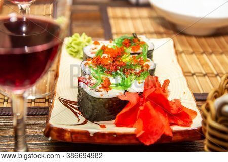Japanese Sushi, Roll With Caviar And Seaweed Chuka, Ginger, Wasabi On A Plate. A Glass Of Red Wine O