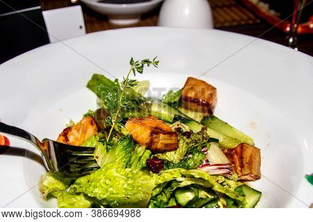 Salad Of Lettuce Leaves, Fish Trout On A White Plate. Fresh, Tasty Dish In The Restaurant.