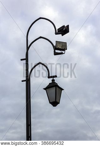 Lamppost With Modern Floodlights And Vintage Lantern Against A Dark Sky With Blue Clouds. Urban Desi