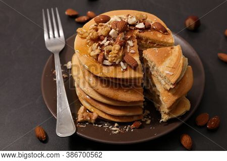 stack of pancake with syrup and nuts