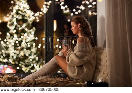 christmas, holiday and people concept - young woman in pullover sitting on windowsill with coffee or tea cup at home over festive lights on background