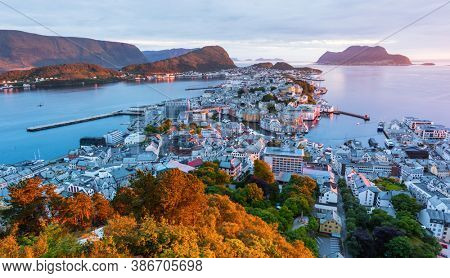 Panorama of colorful sunset in Alesund port town on western coast of Norway. Place where the ocean meet the mountains. Landscape photography