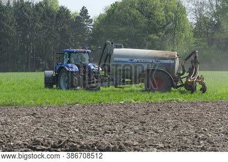 Sint Gillis Waas, Belgium, April 15, 2020, Farmer Is Fertilizing The Field With His Tractor