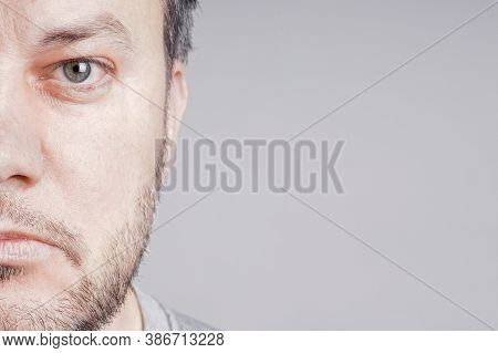 Half Face Of Serious Mid Adult Man Looking At Camera With Copy Space On Gray Background