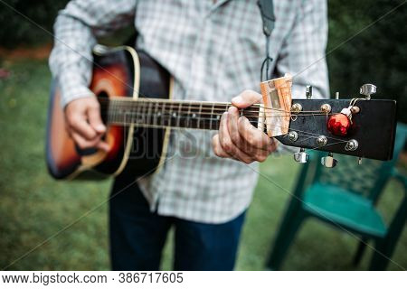 Close-up Of Guitar Player Playing Acoustic Guitar With Money On The Guitar Neck