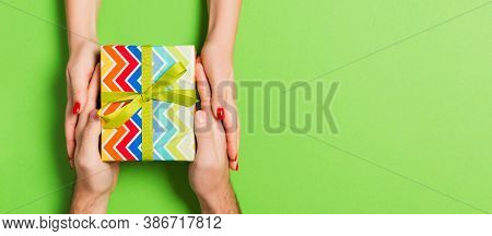 Top View Of A Man And A Woman Giving And Receiving Gift For A Holiday On Colorful Background. Love A