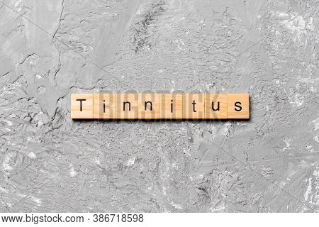 Tinnitus Word Written On Wood Block. Tinnitus Text On Cement Table For Your Desing, Concept