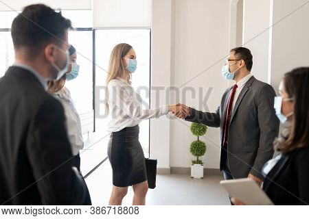 Businessman Shaking Hands With Female Colleague During A Standing Meeting In Office. Business People