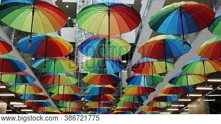 Rainbow Umbrella On The Background Of The Supermarket. Many Multi-colored Umbrellas. Umbrella Decora