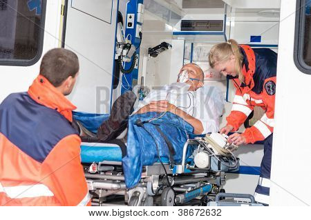 Paramedics putting patient man oxygen mask in ambulance car poster