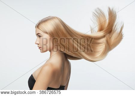Beautiful Model With Long Smooth, Flying Blonde Hair Isolated On White Studio Background. Young Cauc