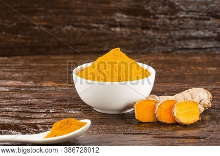 Turmeric Powder And Fresh Turmeric On Wooden Background