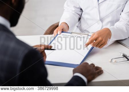 Partial View Of Doctor Pointing With Finger At Insurance Claim Form Near African American Patient Ho