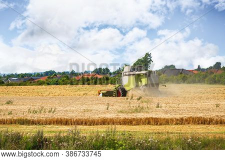 Harvester Near The City On A Golden Field. Dust Flying In The Air Behind A Rural Machine In The Summ