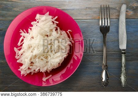 Daikon On Blue Grey Wooden Background. Daikon On Red Plate With Fork And Knife Top View
