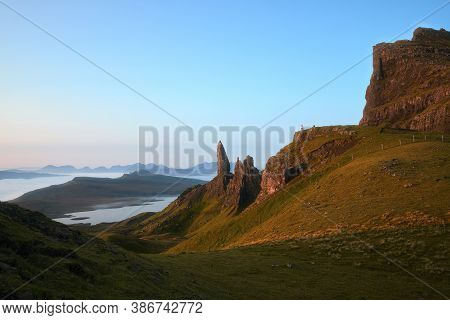 Sunny Landscape Of The High Sharp Cliffs Towering Over The Lake And The Sea In The Morning And Small