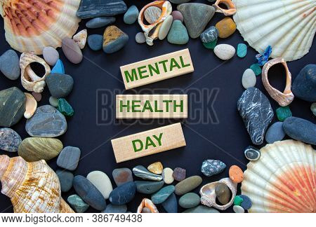 Text 'mental Health Day' On Wooden Blocks On A Beautiful Black Background. Sea Stones And Seashells.