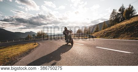Motorcycle rider on the mountain road, wide format. Dramatic sunset sky