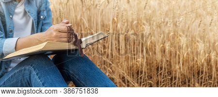 Christian Woman Praying On Holy Bible And Wooden Cross In Barley Field On Summer. Woman Pray For God