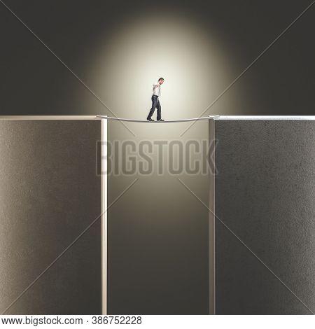 man balances himself to cross a makeshift bridge. concept of challenge and danger.